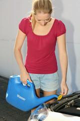 Frau füllt Kühlwasser in Auto