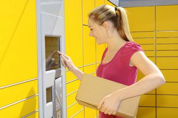 Frau bringt Paket zur Packstation