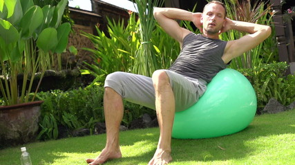 Young man doing sit-ups on fitness ball in garden