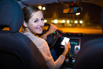 Pretty young woman using her smart phone while driving her car
