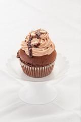 Cupcake al cioccolato su un'alzatina isolato su sfondo bianco