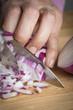 Cortando cebolla con un cuchillo en la cocina sobre la tabla