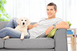 Young guy sitting on couch with a puppy at home
