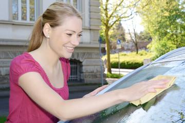 Frau wischt Autoscheibe mit Fensterleder