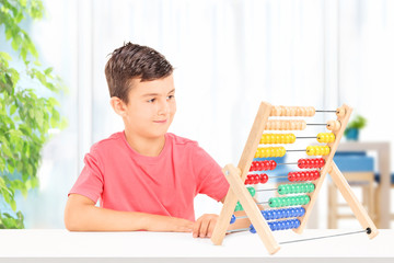 Kid counting with abacus seated on table at home