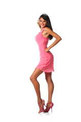 Cute latin woman flirting and smiling in a pink dress in studio