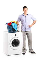 Guy standing by a washing machine