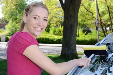 Frau putzt Auto-Scheibe