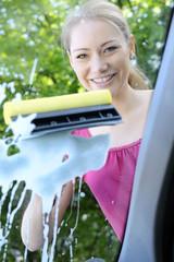 Frau reinigt Windschutzscheibe von Auto