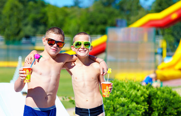 happy teenage boys showing thumbs up in water park