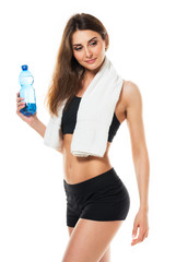 Young athletic girl with a bottle of water and towel on white