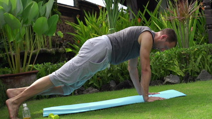 Young man exercising in garden, plank exercise