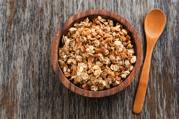 homemade granola in a wooden bowl and spoon, top view