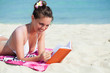 Woman is reading a book on a beach