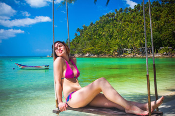 Young woman swings on a tropical beach