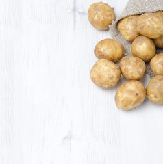 new potatoes in a sack on a white wooden  background