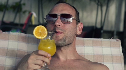 Happy man raising toast with cocktail on sunbed