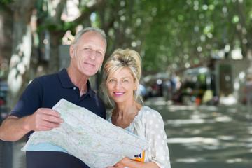 aktives seniorenpaar mit karte in der stadt