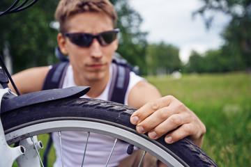 Cyclist checks wheel