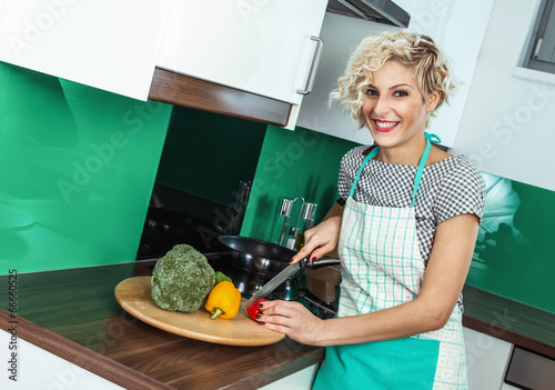 Young woman cooking healthy food at home