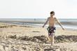 Portrait of teenage is walking on sand near sea