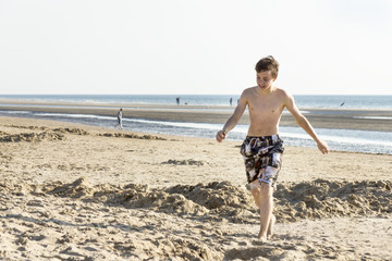 Portrait of teenage is walking on sand near sea