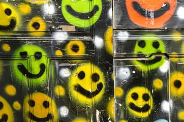 Bunte Smileys an einem Bretterzaun