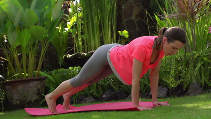 Young woman exercising in the garden