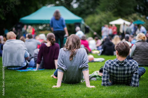 Friends enjoying an outdoors music community event, festival.