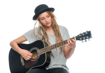 Blonde Frau mit Hut spielt Gitarre