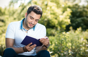 Man sitting on meadow and reading a book