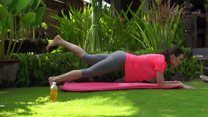 Woman doing plank exercise in the garden