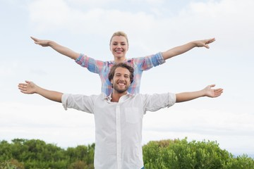 Cute couple standing outside with arms outstretched