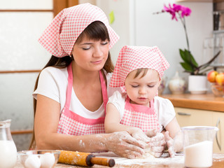 Mother and daughter making cookie dough together at kitchen