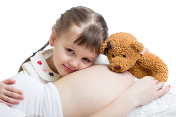 kid girl cuddling pregnant mother's stomach