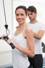 Fit smiling woman using weights machine for arms with her traine
