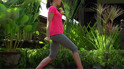 Woman exercising with dumbbells in garden, super slow motion
