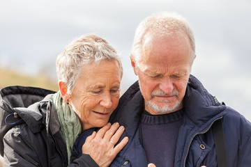 happy elderly senior couple walking on beach
