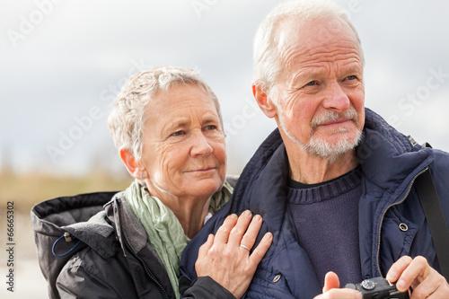 Leinwanddruck Bild happy elderly senior couple walking on beach