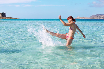 Happy girl splashing the crystal clear water, Sardinia, Italy