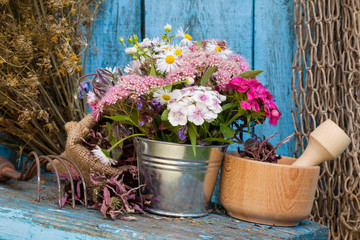 flowers in bucket and mortar with healing herbs