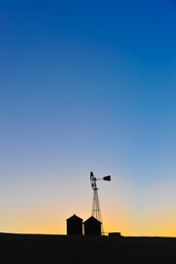 The silhouette of a windmill and buildings