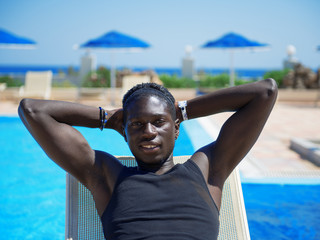 young african man relaxing on beach