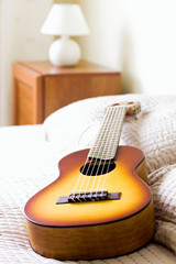 Acoustic guitalele lies on the bed