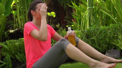Woman resting after workout in garden, super slow motion