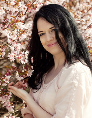 Happy young woman in spring flowers garden lifestyle portrait.