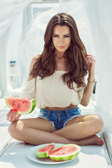 Fashion portrait with a sexy woman with watermelon