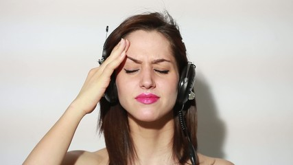 Girl listening to music and having a headache