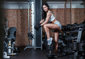 Sexy girl with boxing gloves posing in the gym.