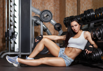 Young sexy woman after workout in gym.